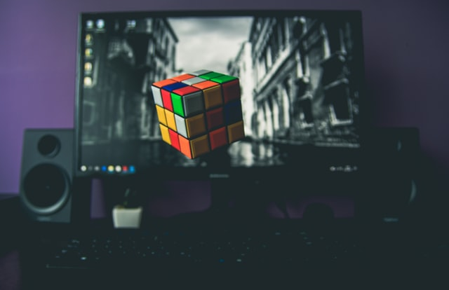black computer speakers with a rubix cube